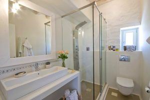 The Villa Chora Deluxe bathroom with basin, toilet and shower. A Luxury villa in Chora, Mykonos.