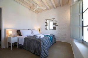 The Villa Chora Deluxe bedroom with open window and sea view. A Luxury villa in Chora, Mykonos.