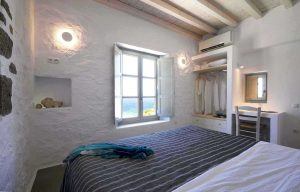 The Villa Chora Deluxe bedroom with open window and sea view. A Luxury villa in Chora, Mykonos.