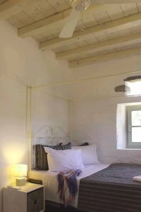 The Villa Chora Deluxe bedroom with double bed and windows. A Luxury villa in Chora, Mykonos.