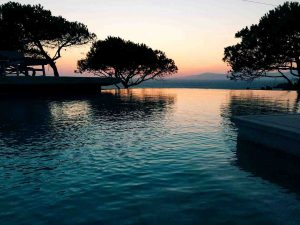 Swimming pool with trees and sea view of the Villa Chora Deluxe. A Luxury villa in Chora, Mykonos