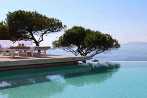 Swimming pool of the Villa Chora Deluxe with trees and a sea view. A Luxury villa in Chora, Mykonos