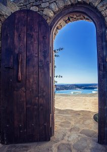 The luxury Villa Italiana arched wooden entrance. A luxury villa in Mykonos with sea view.