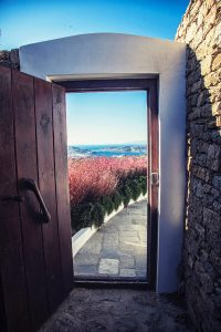 The luxury Villa Italiana wooden entrance. A luxury villa in Mykonos with sea view.