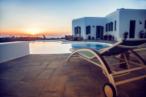 Sun lounger in front of pool of the luxury Villa Italiana. A luxury villa in Mykonos with sea view.