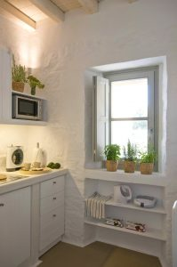 The Villa Chora Deluxe homey kitchen with microwave and window. A Luxury villa in Chora, Mykonos.