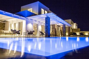 Swimming pool of the Villa Onar & Villa Cloud Luxury retreats in Mykonos, and building by night.