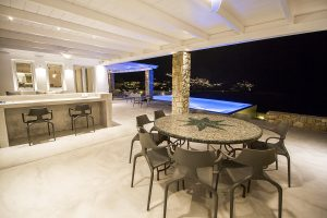 Round table with chairs under the Villa Onar & Villa Cloud Luxury retreats in Mykonos pergola.