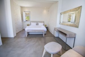 The Villa Onar & Villa Cloud Luxury retreats in Mykonos bedroom with double bed mirror and desk.