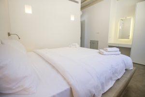 The Villa Onar & Villa Cloud Luxury retreats in Mykonos bedroom with double bed and mirror.