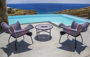 Tables, chairs and L shaped pool of the Villa Onar & Villa Cloud Luxury retreats in Mykonos.