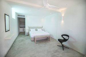 The Villa Onar & Villa Cloud Luxury retreats in Mykonos bedroom with double bed, mirror and window.