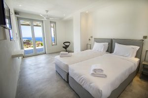The Villa Onar & Villa Cloud Luxury retreats in Mykonos bedroom with twin beds and windows.