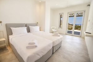 The Villa Onar & Villa Cloud Luxury retreats in Mykonos bedroom with twin beds and window.