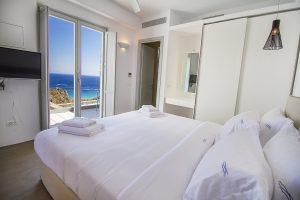 The Villa Onar & Villa Cloud Luxury retreats in Mykonos bedroom with double bed and windows.