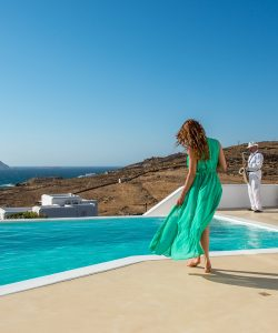 Woman in green dress walking by the swimming pool of the Ftelia Luxury villa rental in Mykonos.