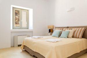Villa Ftelia luxury villa retreat in Mykonos bedroom with double bed, bedside table and window.