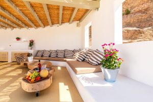 Pergola area of the Ftelia luxury villa rental in Mykonos with coffee tables and built in sofas.
