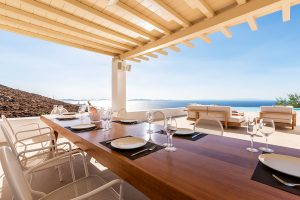 Dinner table and chairs with a view of the sea under the pergola of the Sotavento luxury villa.