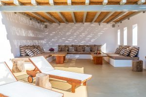 Pergola area of the Ftelia luxury villa rental in Mykonos with sun loungers and built in sofas.