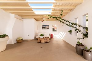 Under the pergola of the Sotavento luxury villa. Wall plants, flower pots and an open roof.