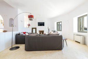 Villa Ftelia luxury villa retreat in Mykonos sitting room with sofas, floor lamp and tv.