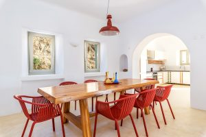 Villa Ftelia luxury villa retreat in Mykonos dining room area with wooden table and red chairs.