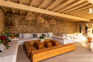 Under the pergola of the Sotavento Luxury Villa Rental in Mykonos. Sofas, coffee tables and plants.