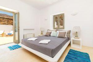 Villa Ftelia luxury villa retreat in Mykonos bedroom with double bed, bedside table and windows.