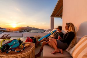 A woman and a man relaxing on the outdoor sofa of the Villa Ftelia luxury villa rental in Mykonos.