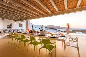 Pergola area of the Ftelia luxury villa rental in Mykonos with dinner table and chairs.