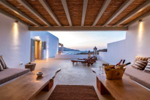 Pergola area of the Ftelia luxury villa rental in Mykonos with sun lounger and sofas.