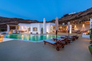 Villa Ftelia luxury villa rental in Mykonos exterior and swimming pool as seen in the evening.