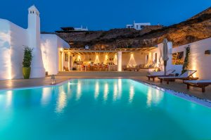 Villa Ftelia luxury villa rental in Mykonos exterior and swimming pool as seen in the evening.