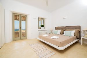 Villa Ftelia luxury villa retreat in Mykonos bedroom with double bed, bedside table and windows.