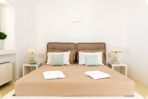 Villa Ftelia luxury villa retreat in Mykonos bedroom with double bed and bedside tables.