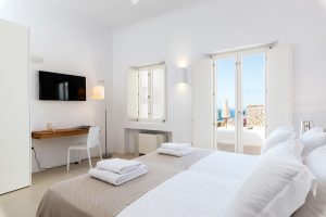 Villa Sotavento VIP luxury villa retreat in Mykonos bedroom with double bed, desk and windows.