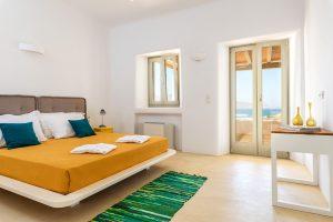Villa Ftelia luxury villa retreat in Mykonos bedroom with double bed, desk and windows.