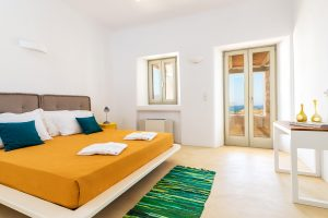 Villa Ftelia luxury villa retreat in Mykonos bedroom with double bed, desk and windows.