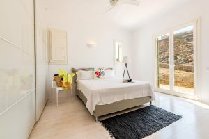 Bedroom with double bed and window of the Villa Kastro Windsurf & Kitesurf retreat in Mykonos.