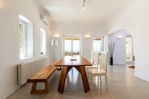 Dining room area with table and chairs of the Villa Kastro Windsurf & Kitesurf retreat in Mykonos.