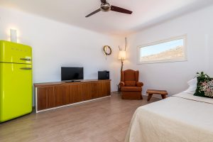 Bedroom with single bed and window of the Villa Kastro Windsurf & Kitesurf retreat in Mykonos.
