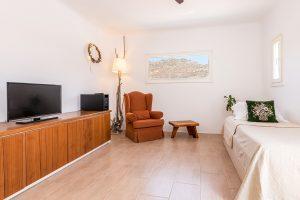 Bedroom with single bed and window of the Villa Kastro Windsurf & Kitesurf retreat in Mykonos.