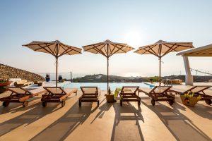 Swimming pool with sunbeds and umbrellas of the Villa Kastro Windsurf & Kitesurf retreat in Mykonos.