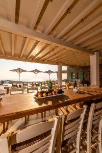 Outdoor dinner table, chairs & umbrellas of the Villa Kastro Windsurf & Kitesurf retreat in Mykonos.