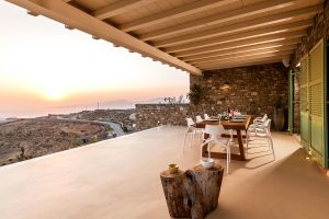 Large table and chairs of the Villa Kastro Windsurf & Kitesurf retreat in Mykonos.