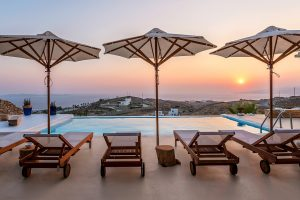 Swimming pool with sunbeds and umbrellas of the Villa Kastro Windsurf & Kitesurf retreat in Mykonos.