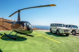 Villa Ftelia luxury villa rental in Mykonos helipad and parking area with 2 cars and a helicopter.