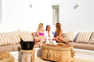 Two ladies and a man sitting on a sofa of the Villa Ftelia luxury villa rental in Mykonos.