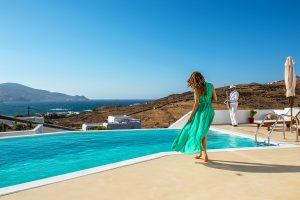 A woman wearing a green summer dress, standing in front of the Ftelia luxury villa rental in Mykonos